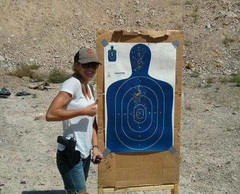 Cassie standing next to gun target practice poster