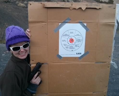 Lacie with gun target practice paper