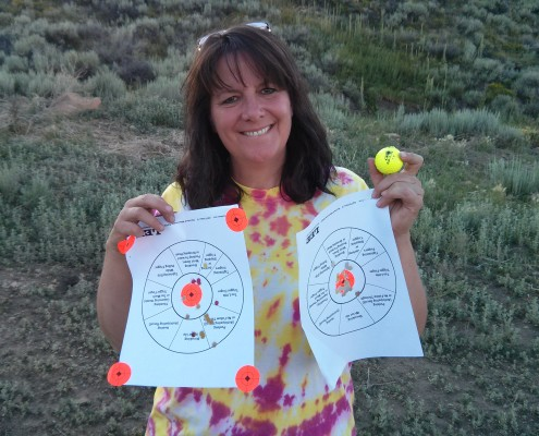 Michele holding shooting range target papers
